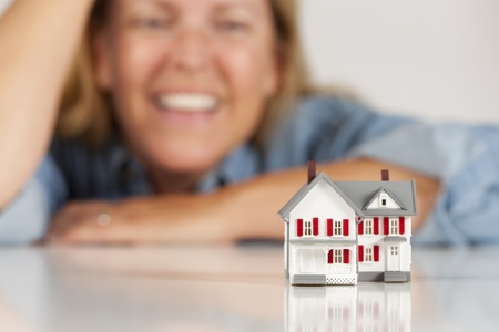 Smiling Woman Leaning on Hands Behind Model House on a White Surface. photo
