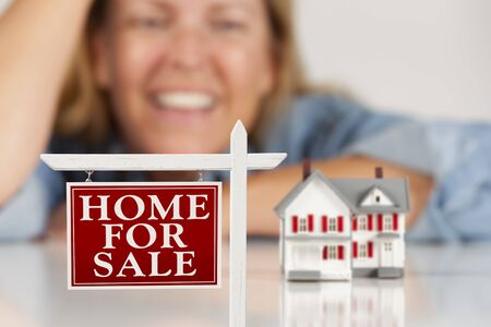 Lachende vrouw leunend op handen achter Home Te koop Real Estate Sign en Model Huis op een wit vlak. Stockfoto