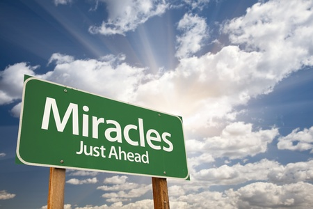 miracles: Miracles Green Road Sign Against Clouds and Sunburst.