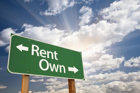Rent, Own Green Road Sign Against Clouds and Sunburst. Reklamní fotografie - 9812575