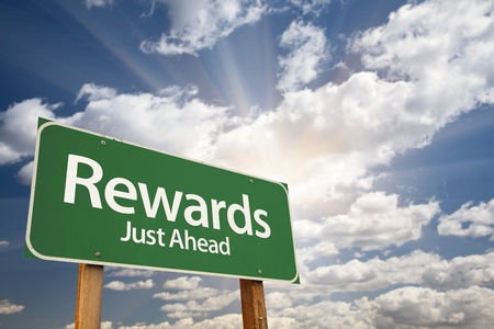 just ahead: Rewards Green Road Sign Against Clouds and Sunburst.