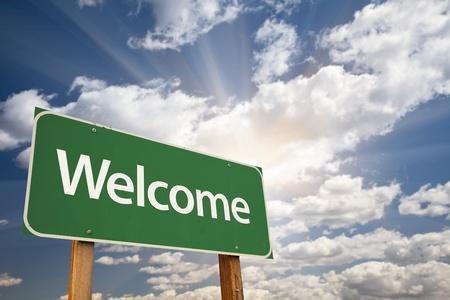 bienvenida: Bienvenida se�al verde contra nubes y Sunburst. Foto de archivo