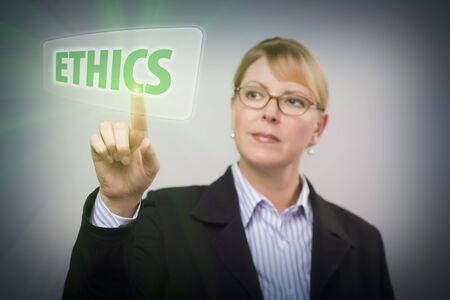 principles: Attractive Blonde Woman Pushing Ethics Button on an Interactive Touch Screen. Stock Photo