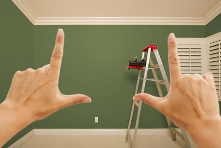 Hands Framing Green Painted Room Wall Interior with Ladder, Paint Bucket and Rollers.