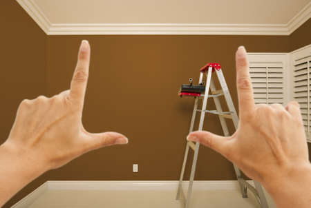 Hands Framing Brown Painted Room Wall Interior with Ladder, Paint Bucket and Rollers. photo