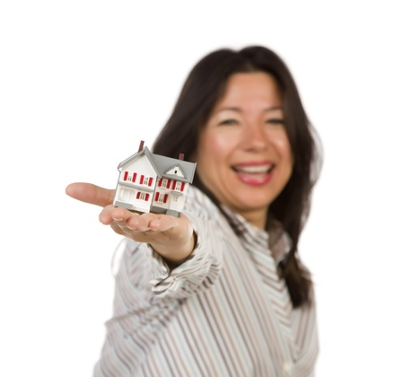 Attractive Multiethnic Woman Holding a Small House Out In Front of Her Isolated on a White Background. photo