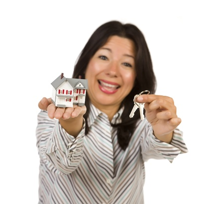Attractive Multiethnic Woman Holding Small House and Keys Isolated on a White Background - Focus is on the house and keys. photo