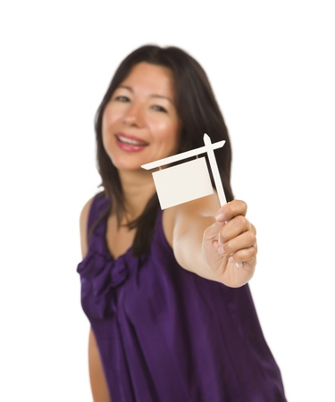Attractive Multiethnic Woman Holding Blank Small Real Estate Sign in Hand Isolated on White Background Ready for Your Own Message. photo