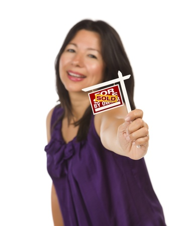 Attractive Multiethnic Woman Holding Small Sold For Sale By Owner Real Estate Sign in Hand Isolated on White Background. Stock Photo