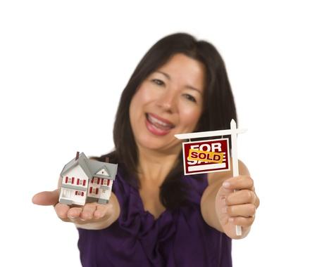 sold small: Donna multietnica Holding Small venduti per vendita immobiliare segno e casa in mano isolato su sfondo bianco.