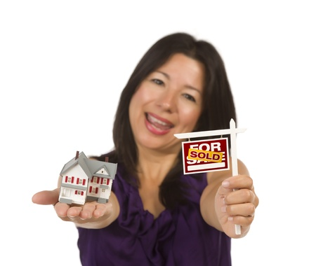 Multiethnic Woman Holding Small Sold For Sale Real Estate Sign and House in Hand Isolated on White Background. Stock Photo