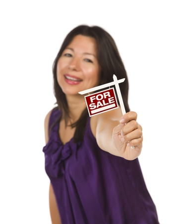 Attractive Multiethnic Woman Holding Small For Sale Real Estate Sign in Hand Isolated on White Background. photo