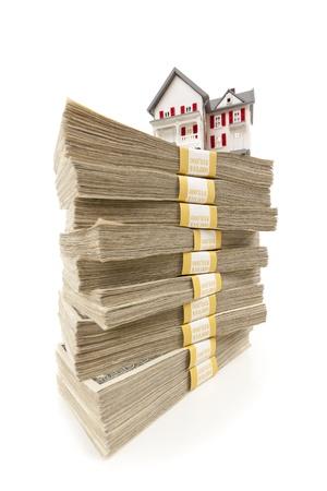 20: Peque�a casa en pilas de cien billetes de d�lar aisladas sobre fondo blanco. Foto de archivo