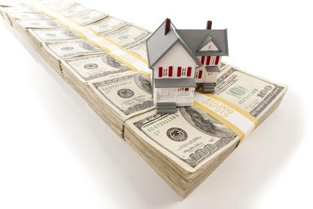 equidad: Peque�a casa en pilas de cientos de billetes de d�lares aislados en un fondo blanco.