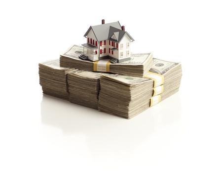 equidad: Peque�a casa en pilas de cien billetes de d�lar aisladas sobre fondo blanco. Foto de archivo
