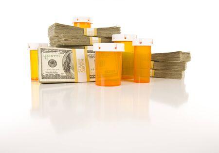 薬のびんと反射面の上のドルの何百ものスタックを空に。