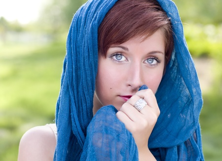 Outdoor Portrait of Pretty Blue Eyed Young Red Haired Adult Female with Blue Scarf. Фото со стока