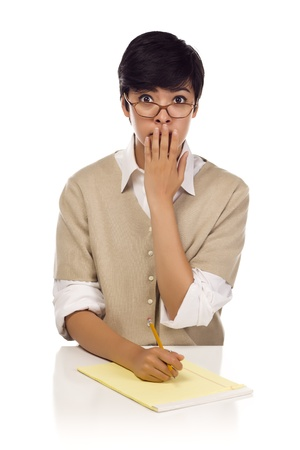 embarrassed: Shocked Mixed Race Young Adult Female Student at Table with Pad of Paper and Pencil Isolated on a White Background. Stock Photo
