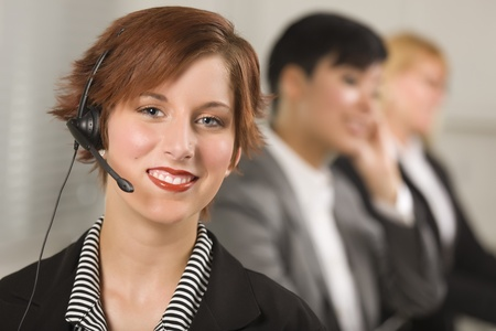Pretty Red Haired Businesswoman with Headset and Colleagues Behind in Office Setting. photo