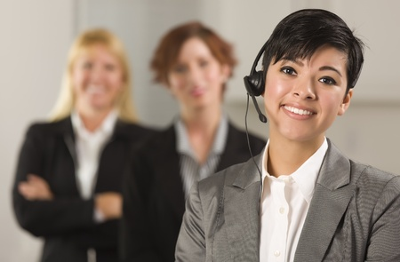 working at office: Pretty Hispanic Businesswoman with Colleagues Behind in an Office Setting.