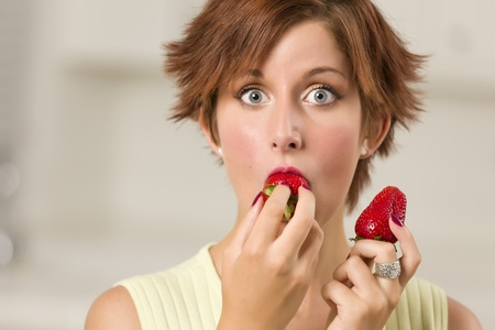 red haired woman: Pretty Wide-eyed Red Haired Woman Biting Strawberry in Her Kitchen. Stock Photo