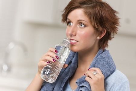 red haired woman: Pretty Red Haired Woman with Towel Drinking From Water Bottle in Her Kitchen.