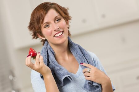Pretty Red Haired Woman with Towel Holding Strawberry in Her Kitchen. photo
