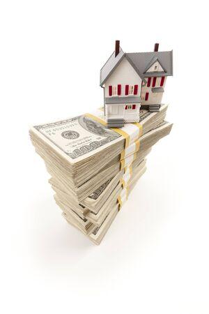 Kleine Huis op Stapels van honderd dollar biljetten Geà ¯ soleerd op een witte achtergrond. Stockfoto