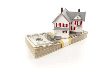 in escrow: Small House on Stack of Hundred Dollar Bills Isolated on a White Background.