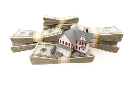 in escrow: Small House with Stacks of Hundred Dollar Bills Isolated on a White Background.