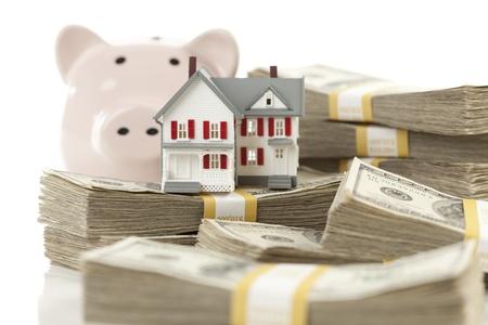 Kleine Huis en Piggy Bank met stapels van honderd dollar biljetten Geà ¯ soleerd op een witte achtergrond.