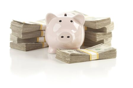 Pink Piggy Bank with Stacks of Hundreds of Dollars Isolated on a White Background. photo