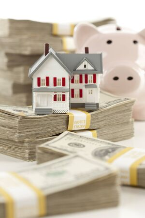 Small House and Piggy Bank with Stacks of Hundred Dollar Bills Isolated on a White Background. photo