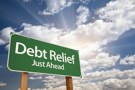 Debt Relief, Just Ahead Road Sign verde sopra il cielo minaccioso, Nuvole e Sunburst. Archivio Fotografico