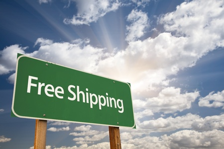 enticement: Free Shipping Green Road Sign Over Dramatic Sky, Clouds and Sunburst. Stock Photo