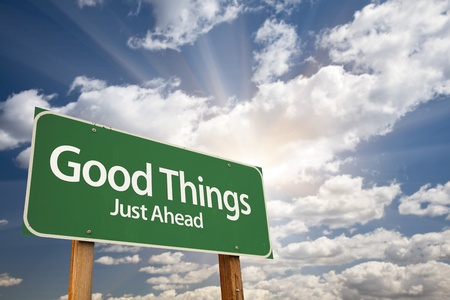 just ahead: Good Things, Just Ahead Green Road Sign Over Dramatic Sky, Clouds and Sunburst. Stock Photo