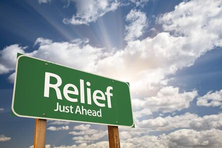 lull: Relief, Just Ahead Green Road Sign Over Dramatic Sky, Clouds and Sunburst. Stock Photo