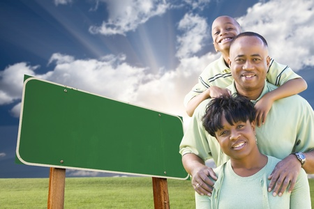 Attractive African American Family in Front of Blank Green Road Sign Ready for Your Own Message. 版權商用圖片