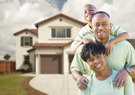 fachada de casa: Familia afroamericana atractiva delante de casa hermosa.