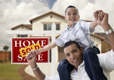 Happy Hispanic Father and Son in Front of New House and Sold Real Estate Sign. photo