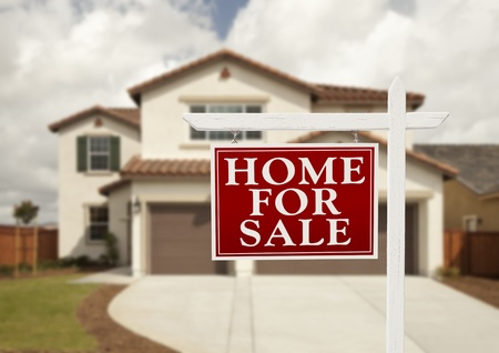 Home For Sale Real Estate Sign in Front of New House. Stock Photo