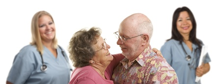 Happy Loving Senior Couple with Smiling Medical Doctors or Nurses Behind Isolated on a White Background. photo