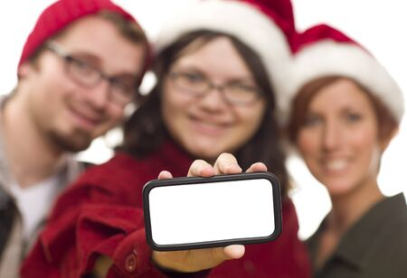 Girl with Friends and Santa Hats Holding Blank White Smart Phone - Ready for Your Own Message. photo
