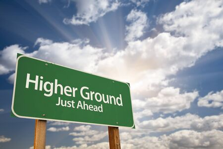 values: Higher Ground Green Road Sign Against Dramatic Sky, Clouds and Sunburst.