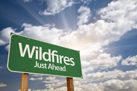 highs: Wildfires Green Road Sign Against Dramatic Sky, Clouds and Sunburst. Stock Photo