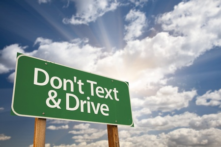 Dont text and Drive Green Road Sign with Dramatic Sky, Clouds and Sun. photo