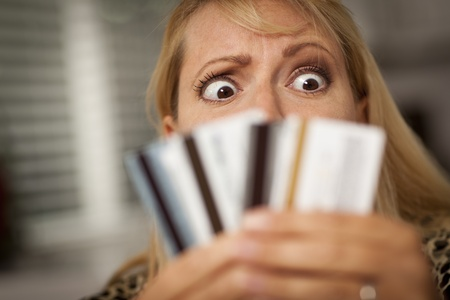Upset Robed Woman Glaring At Her Many Credit Cards. photo