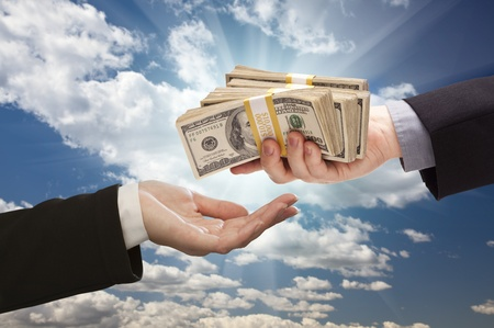 hands giving: Handing Over Cash with Dramatic Clouds and Sky Background.