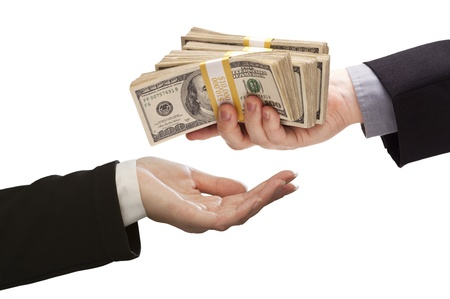Handing Over Stacks of Cash to Other Hand Isolated on a White Background. photo