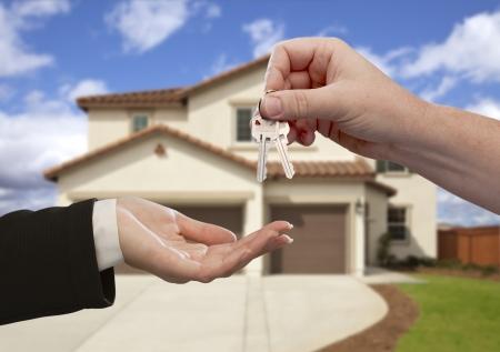 real estate sold: Entrega de las llaves de la casa en frente de una hermosa casa nueva.